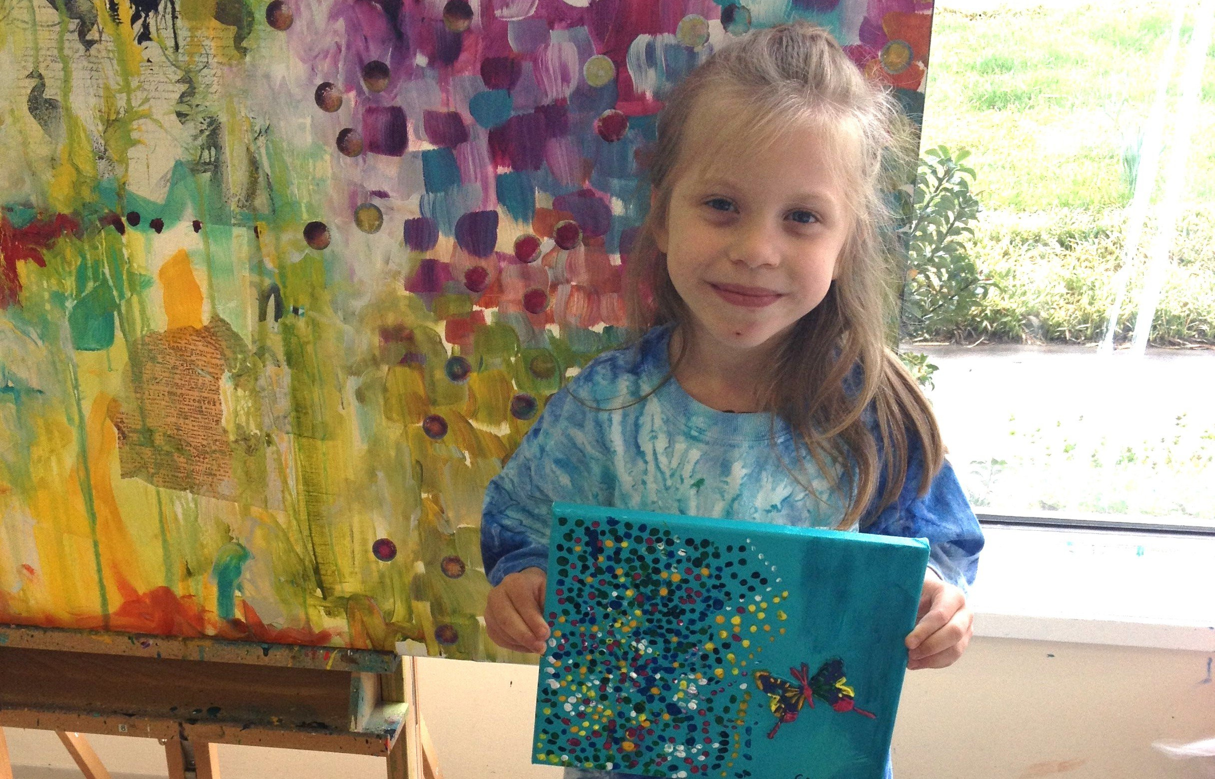 A little girl holds a blue painting with a butterfly and dots while standing in front of a colorful painting.