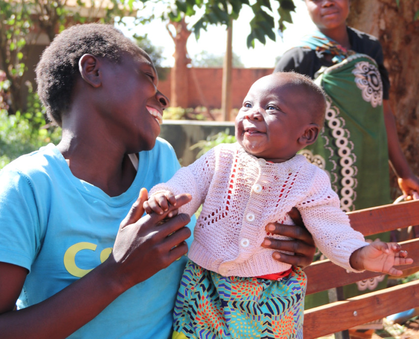 The first child to receive the malaria vaccine is smiling at her mother.